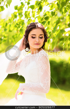 Beautiful bride in white dress in the spring or summer garden stock photo, Beautiful bride in white dress in the spring or summer garden by Satura86