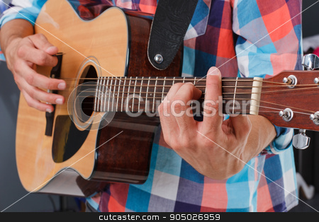 Acoustic guitar being played. stock photo, Acoustic guitar being played. Fingers holding fingerboard. Man's hand holding fingerboard. by Denys