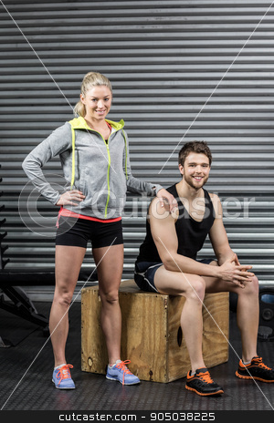 Portrait of smiling fit couple stock photo, Portrait of smiling fit couple at crossfit gym by Wavebreak Media