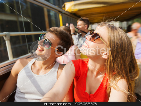 happy teenage couple traveling by tour bus stock photo, travel, tourism, summer vacation, sightseeing and people concept - happy teenage couple in sunglasses traveling by tour bus by Syda Productions