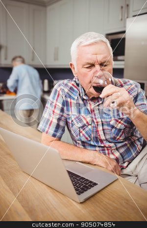 Senior man drinking red wine while using laptop stock photo, Senior man drinking red wine while using laptop and woman working in kitchen behind him by Wavebreak Media