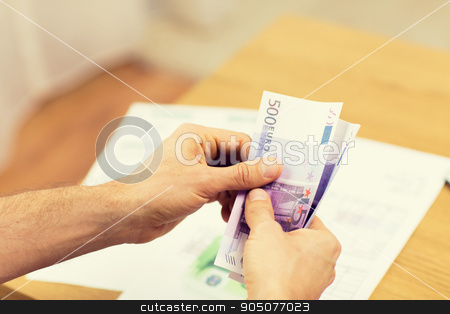 close up of man hands counting money at home stock photo, savings, finances, economy and home concept - close up of man hands counting money at home by Syda Productions
