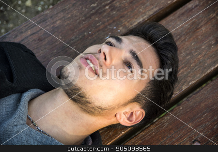 Close-up of young man lying on bench and looking up stock photo, Close-up of young man relaxing on bench and looking up, smiling by Stefano Cavoretto