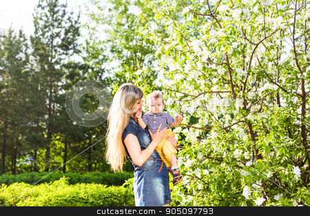 Happy woman and child in the blooming spring garden.  Mothers day holiday concept stock photo, Happy woman and child in the blooming spring garden.Child kissing woman. Mothers day holiday concept by Satura86