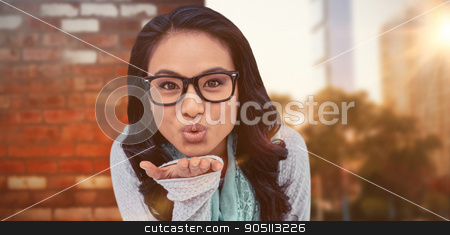 Composite image of asian woman blowing kiss to the camera stock photo, Asian woman blowing kiss to the camera against wall of a house by Wavebreak Media