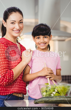 Portrait of smiling mother and daughter preparing salad stock photo, Portrait of smiling mother and daughter preparing salad at home by Wavebreak Media