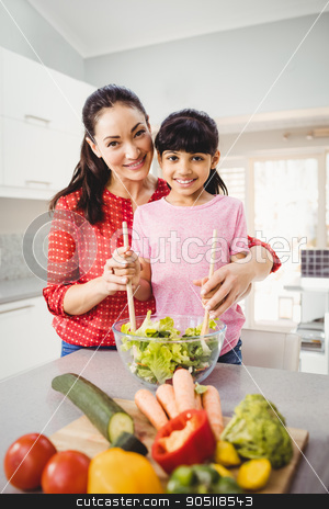 Portrait of smiling mother and daughter preparing vegetable sala stock photo, Portrait of smiling mother and daughter preparing vegetable salad at home by Wavebreak Media