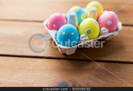 close up of colored easter eggs in egg box stock photo, easter, holidays, tradition and object concept - close up of colored easter eggs in egg box or carton wooden surface by Syda Productions