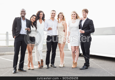 Well dressed people posing next to a limousine stock photo, Well dressed people posing next to a limousine on a night out by Wavebreak Media