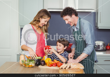 Smiling parents with son in kitchen stock photo, Son holding bell pepper with parents in kitchen at home by Wavebreak Media