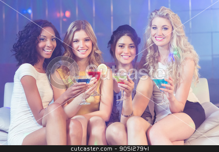 Pretty girls with cocktails stock photo, Pretty girls with cocktails in a club by Wavebreak Media
