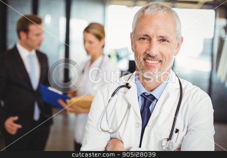 Portrait of a smiling male doctor in hospital  stock photo, Portrait of a smiling male doctor standing in the hospital by Wavebreak Media