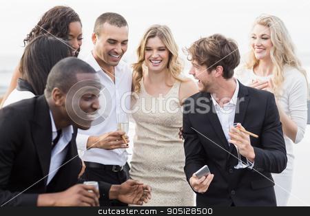 Well dressed people looking smartphone stock photo, Well dressed people looking smartphone on a night out by Wavebreak Media