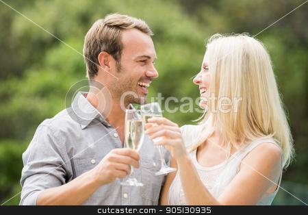 Smiling couple toasting champagne flutes  stock photo, Smiling couple toasting champagne flutes at resort by Wavebreak Media