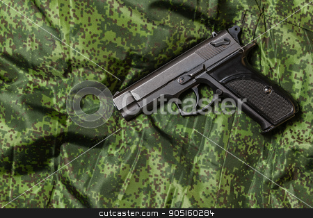 semi-automatic pistol on pixel camouflage background stock photo, Weathered generic russian soviet semi-automatic 9mm pistol on pixel camouflage background by Denys Kornylov