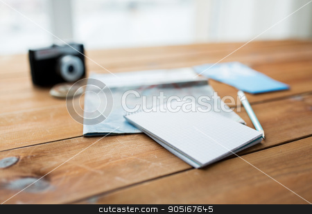 close up of notepad with map and travel tickets stock photo, vacation, tourism, travel and objects concept - close up of blank notepad with map and airplane tickets by Syda Productions