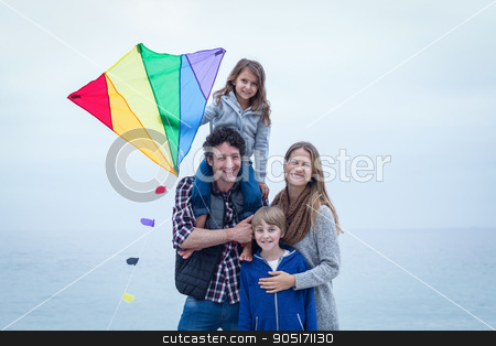 Cheerful family with kite at sea shore stock photo, Portrait of cheerful family with kite at sea shore by Wavebreak Media