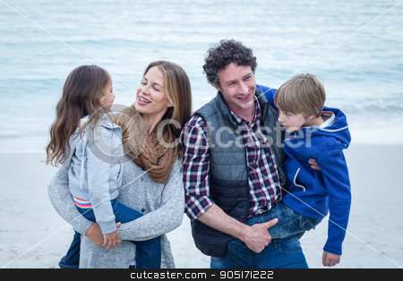 Parents carrying children while enjoying at beach stock photo, Cheerful parents carrying children while enjoying at beach by Wavebreak Media