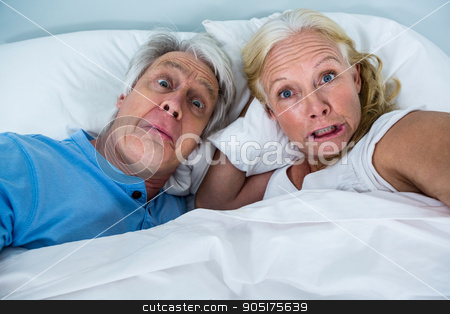 Retired couple making faces while relaxing on bed stock photo, Portrait of retired couple making faces while relaxing on bed in bedroom by Wavebreak Media