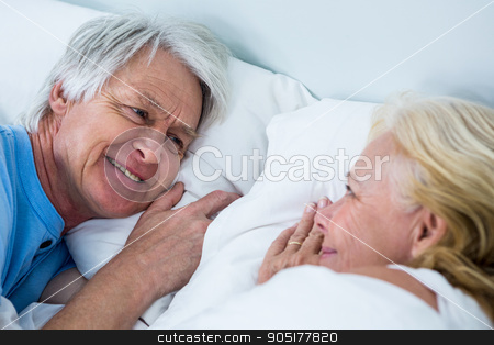 Close-up of smiling senior couple sleeping on bed stock photo, Close-up of smiling senior couple sleeping on bed in bedroom by Wavebreak Media