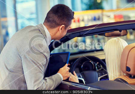 woman and car dealer with tablet pc in auto salon stock photo, auto business, car sale, technology and people concept - woman and car dealer with tablet pc computer in auto show or salon by Syda Productions
