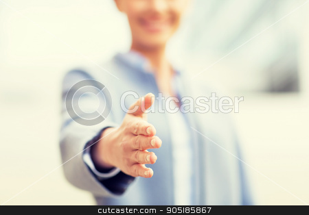 close up of woman giving hand for handshake stock photo, business, partnership, cooperation and people concept - close up of businesswoman giving hand for handshake over office building by Syda Productions