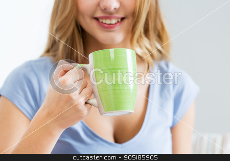 happy woman or teen girl drinking tea from cup stock photo, people and drinks concept - close up of happy woman or teen girl drinking tea from cup by Syda Productions