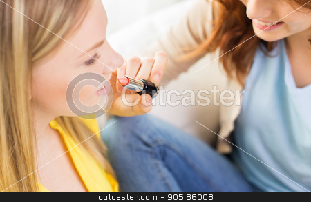 close up of visagist woman applying lipstick stock photo, beauty, make up, cosmetics and people concept - close up of smiling young woman face and visagist or friend applying lipstick by Syda Productions