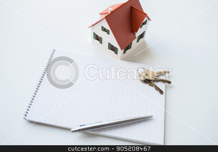 close up of home model, house keys and notebook stock photo,  building, mortgage, real estate and property concept - close up of home model, house keys and notebook with pen by Syda Productions