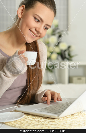 Beautiful Woman Using Laptop stock photo, Young Beautiful Woman with cup of coffee Using Laptop, Indoors by Ruslan Huzau