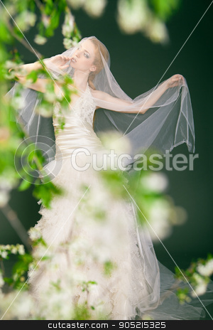 Dreamy beautiful blonde bride walking alone in the park stock photo, Dreamy beautiful blonde bride walking alone in the park enjoying wind wave and dance by Isaeva Iuliia