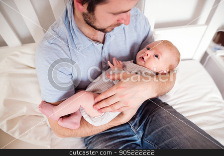 Young father holding his newborn baby son, home bedroom stock photo, Young father holding his cute newborn baby son, home bedroom by HalfPoint