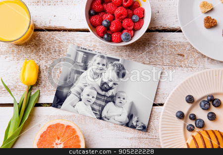 Fathers day composition. Black-and-white picture and breakfast stock photo, Fathers day composition. Black-and-white pictures of father holding her little daughters and a breakfast meal. Studio shot on white wooden background by HalfPoint
