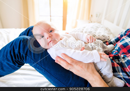 Baby boy held by his father sitting on bed stock photo, Cute newborn baby boy held by his father sitting on bed by HalfPoint