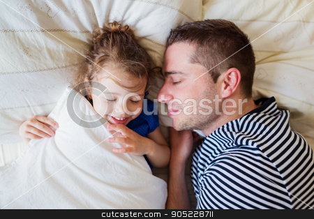 Father and daughter lying in parents bed, sleeping, smiling stock photo, Father and daughter lying in parents bed, sleeping and smiling by HalfPoint