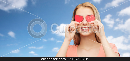 happy young woman with red heart shapes on eyes stock photo, love, romance, valentines day and people concept - smiling young woman or teenage girl with red heart shapes on eyes over blue sky and clouds background by Syda Productions