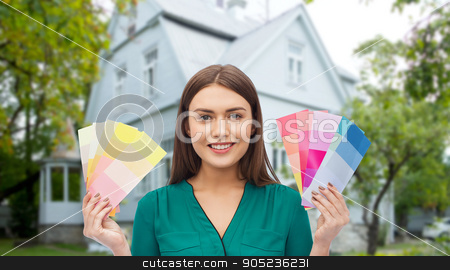 smiling young woman with color swatches stock photo, repair, renovation, decoration, design and people concept - smiling young woman with color swatches or samples over home background by Syda Productions