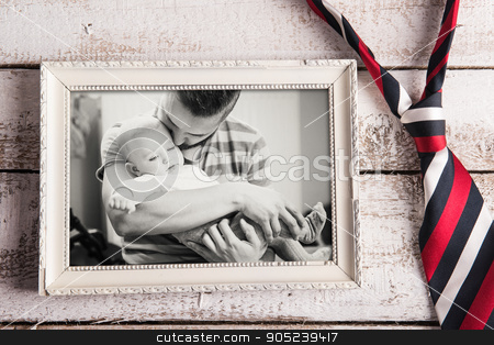Fathers day composition. Picture frame, photo, tie. Wooden backg stock photo, Fathers day composition. Black and white picture of father and daugter in picture frame, colorful tie. Wooden background. Studio shot on wooden background by HalfPoint
