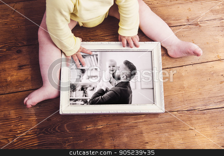 Fathers day composition. Picture frame. Wooden background stock photo, Fathers day composition. Unrecognizable baby holding a photo of father and daughter in white picture frame. Studio shot on wooden background by HalfPoint
