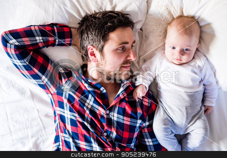 Baby boy lying on bed, next to his father stock photo, Cute newborn baby boy lying on a bed, next to his father by HalfPoint