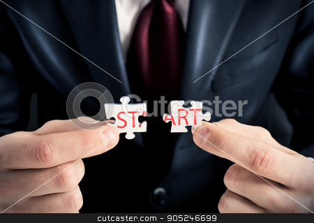 Puzzle start stock photo, Businessman joins two pieces of the puzzle by Federico Caputo