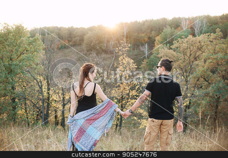 man and pregnant woman hugging holding hands on the background of wild nature, autumn. love story stock photo, man in a black T-shirt and a pregnant woman in a black dress and dreadlocks embrace and are kept in hand, against the background of wild nature, autumn. love story by alexsfoto