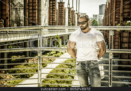 Handsome muscular man standing in city setting stock photo, Handsome muscular blond man standing in city setting or former industrial environment by Stefano Cavoretto