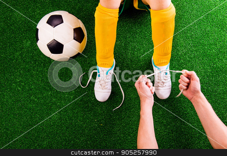 Unrecognizable father tying shoelaces to his son, football playe stock photo, Legs of unrecognizable little football player in yellow knee socks with soccer ball having his shoelaces tied by his father, against artificial grass. Studio shot on green background by HalfPoint