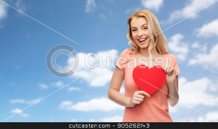 happy woman or teen girl with red heart shape stock photo, love, romance, charity, valentines day and people concept - smiling young woman or teenage girl with blank red heart shape over blue sky and clouds background by Syda Productions