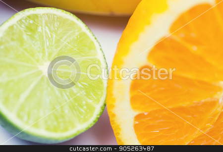 close up of fresh juicy orange and lime stock photo, healthy eating, food, fruits and diet concept - close up of fresh juicy orange and lime by Syda Productions