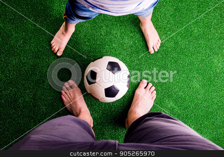 Father and son with soccer ball against green grass stock photo, Legs of unrecognizable father and son with soccer ball, against artificial grass. Studio shot on green background by HalfPoint