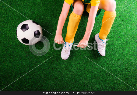 Unrecognizable little football player against green grass, studi stock photo, Unrecognizable little football player with soccer ball tying shoelaces, against artificial grass. Studio shot on green grass. Copy space by HalfPoint