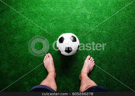 Barefoot football player against green grass, studio shot stock photo, Legs of unrecognizable barefoot football player against artificial grass. Studio shot on green grass by HalfPoint