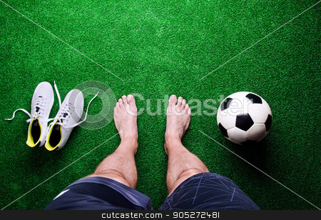 Barefoot football player against green grass, studio shot stock photo, Legs of unrecognizable barefoot football player against artificial grass. Soccer ball, cleats. Studio shot on green grass. Copy space by HalfPoint